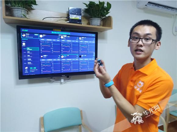 工作人员介绍照护平台以及手环的工作原理.记者张勇 摄