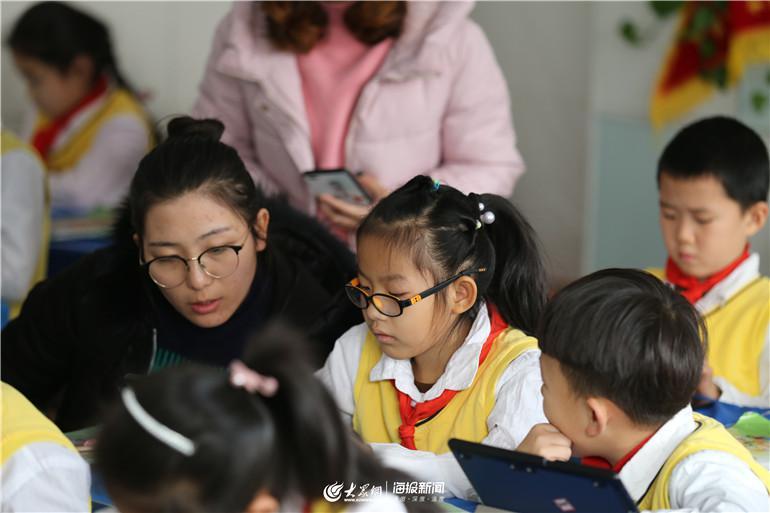 老师在校内辅导学生做家庭作业.
