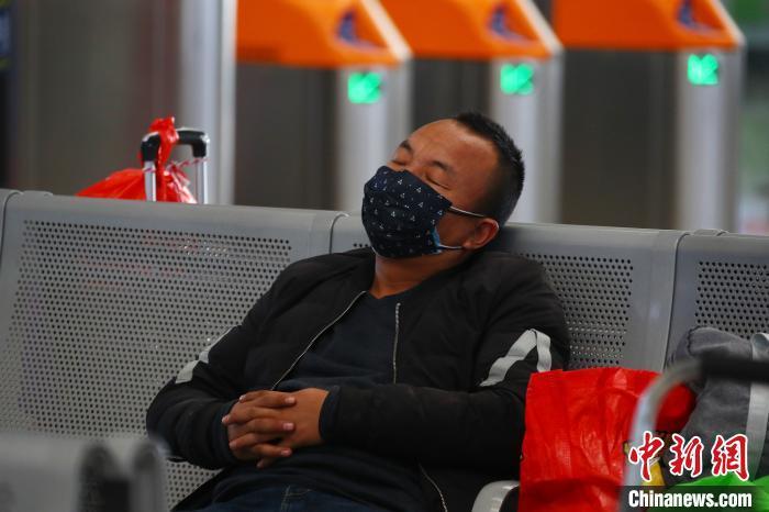南昌西站候车大厅内,戴着口罩打盹的旅客.刘占昆 摄